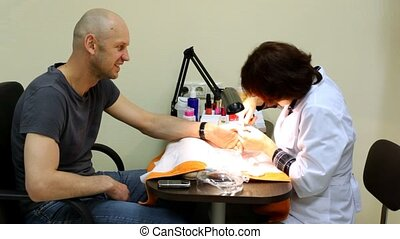 Manicure technician deletes man cuticle by pincers for...