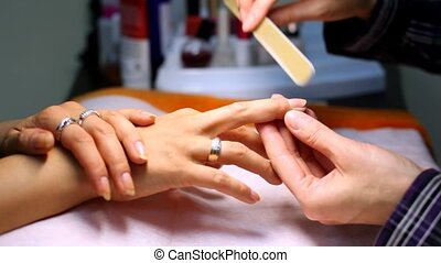 Manicure technician does manicure for client by means of file for nails
