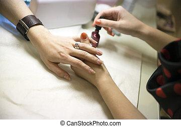 manicure treatment of female hands in beauty salon