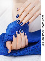 manicure with a blue knitted scarf