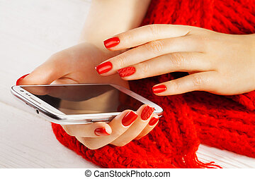 manicure with smartphone and red knitted scarf