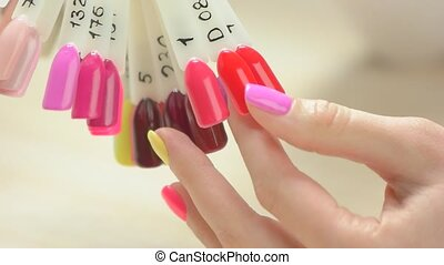 Manicured hand and nail color samples. Young woman hand with...