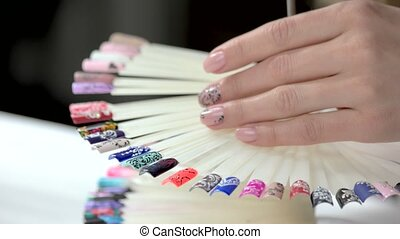 Manicured hand and wheel of nail samples. Turning nail art...