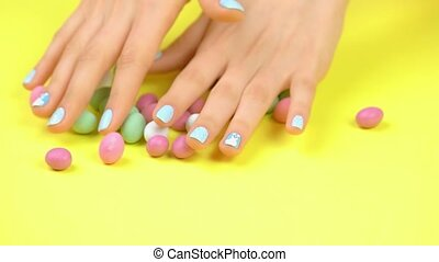 Manicured hands and multicolored caramel candies. Girl hands...