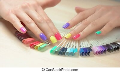 Manicured hands and nail polish palette. Girl hands choosing...