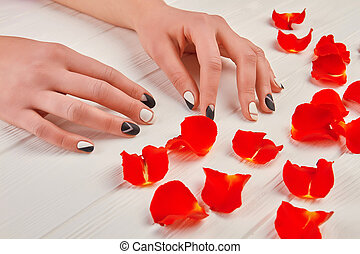 Manicured hands and red petals.