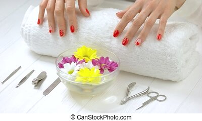 Manicured hands gently touching white towel. Young woman...