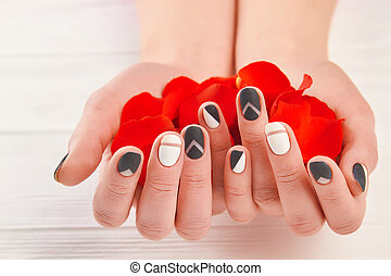 Manicured hands holding red petals.
