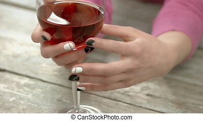 Manicured hands holding wine glass. Woman hands with short...