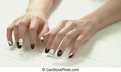 Manicured hands knocking on table. Young woman hands with...