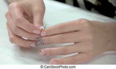 Manicured hands putting on ring. Young woman hands with...