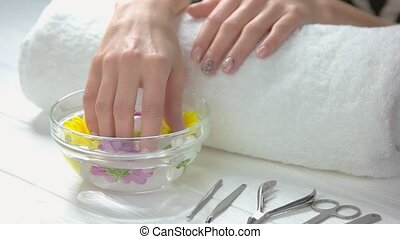 Manicured hands receiving spa treatment. Beautiful female hands in aroma bath. Woman hands in glass bowl with water and flowers. Manicure and hands spa.