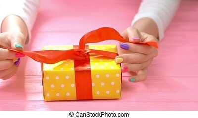 Manicured hands untied ribbon on gift box. Young woman hands...