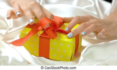 Manicured hands untied ribbon on gift box. Beautiful female...
