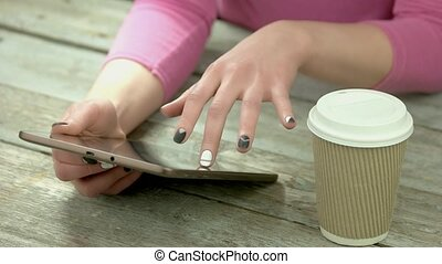 Manicured hands using computer tablet. Young woman hands...
