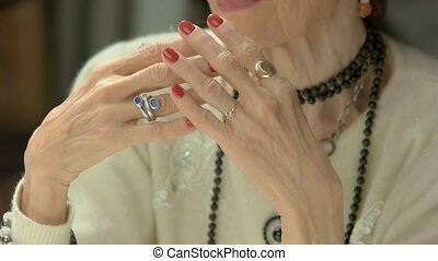 Manicured hands with luxury jewelry. Senior woman...