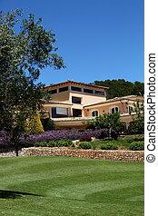 Manicured lawns below a clubhouse - Manicured lush green...
