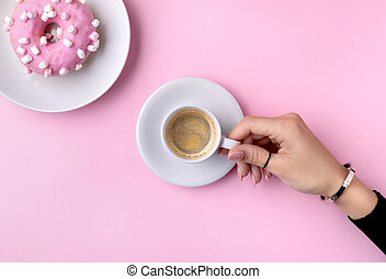 Manicured woman's hand holding white cup of coffee