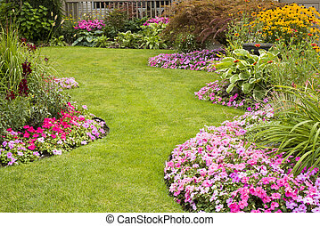 A beautifully manicured yard with a garden full of perennials and annuals.