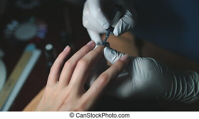 Manicurist Applying Gel Polish on Client Lady Nails. Cosmetic Master in White Gloves Makes Professional Manicure on Woman Fingernails. Aerial View Close Up, Slow Motion, Footage Shot in 4K (UHD)