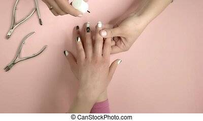 Manicurist applying oil on female nails. Nail beautician...