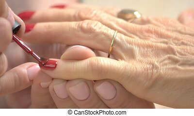 Manicurist applying red varnish with applicator. Close up...