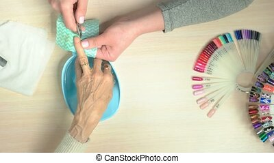 Manicurist cutting the cuticle, top view. Female nail beautician doing manicure to old woman in nail salon. Skin and nail care.