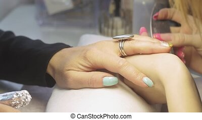 Manicurist file down top cover from nails by hard nail file...