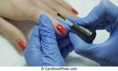 Manicurist gets a top coating on the nail