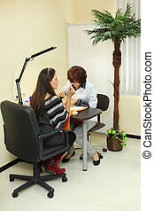 Manicurist makes manicure for woman in beauty salon; client sits with her back to camera; client looks at her hand