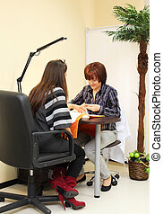 Manicurist makes manicure for woman in beauty salon; client sits with her back to camera