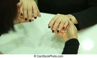 Manicurist does a manicure to the client. Apply gold and black manicure on nails
