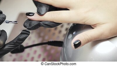 Manicurist master in gloves is covering painting client's nails black shellac, hands closeup. Professional manicure for woman in beauty salon. Hygiene and care for hands. Beauty industry concept.