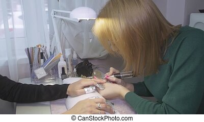Manicurist polish surface of nails to attractive woman by...