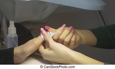 Manicurist wraps fingers of woman by foil in beauty saloon. Nail shellac removal. Manicure