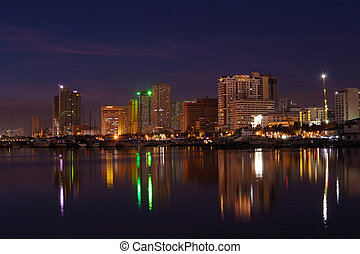 vibrant manila bay city nightscape and building reflections.