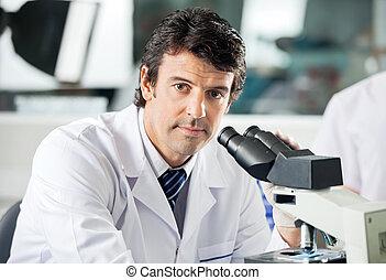 manlig, forskare, användande, mikroskop, in, labb