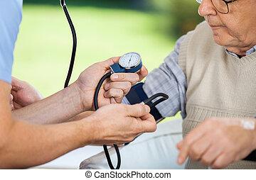 manlig, vaktmästare, mätande blodtryck, av, äldre bemanna