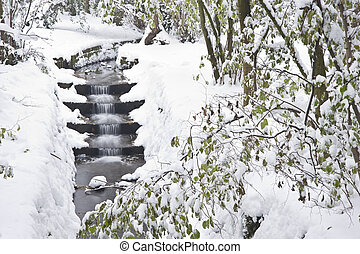 Manmade waterfall cascade through forest ith deep Winter snow