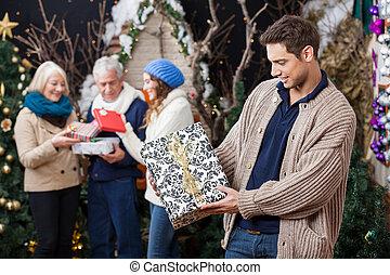 mann, anschauen, weihnachtsgeschenk, mit, familie hintergrund