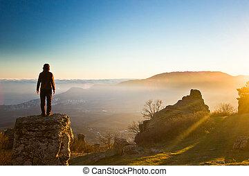 mann, auf, der, felsformation, in, berge, an, sonnenuntergang