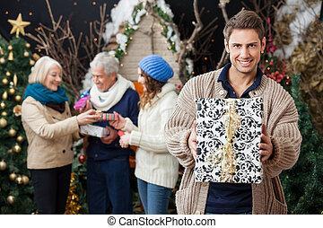 mann, besitz, weihnachtsgeschenk, mit, familie hintergrund