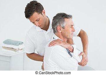 mann, chiropraktiker, untersuchen, fälliger mann