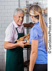 mann, eigentümer, assistieren, weibliche , kunde, in, kaufende muffinkuchen