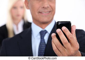 mann, gebrauchend, a, cellphone, mit, seine, assistent, in, der, hintergrund