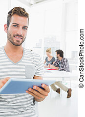 mann, gebrauchend, digital tablette, mit, kollegen, in, hintergrund