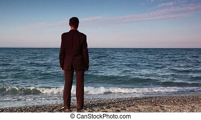 mann, in, klage, stehende , auf, sandstrand, kieselsteine