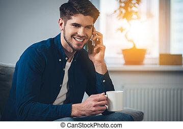 mann, kaffeetasse, beweglich, sitzen, junger, you!, couch, sprechende , während, hören, besitz, lächeln, daheim, nett, telefon, hübsch