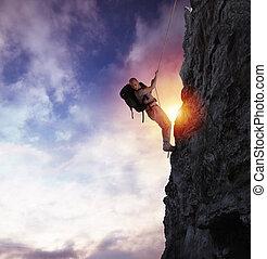 mann, klettert, a, hoch, gefahr, berg, mit, a, seil, während, sonnenuntergang