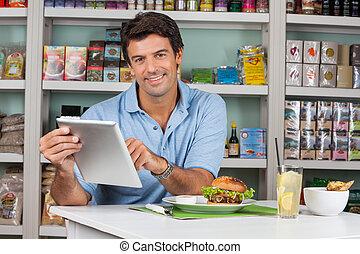 mann, kunde, mit, knabberzeug, gebrauchend, digital tablette, in, supermarkt